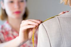 Dressmaker at work. Young blonde needlewoman taking measures of client Stock Images