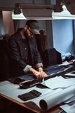 Dressmaker is working on his own project at his atelier. Fashion designer is measuring jeans at his atelier. He is wearing denim, cap and glasses. There are of stock photos