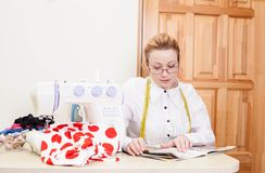 Dressmaker in a workroom. Dressmaker reading a magazine at workplace royalty free stock images