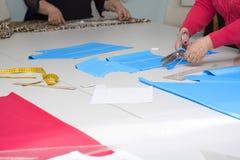 Dressmakers cutting fabric Stock Photos