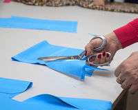 Dressmakers cutting fabric Royalty Free Stock Images