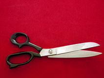 Dressmaking aka tailor scissors on red fabric Stock Image