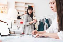 Dressmaster 2 молодых женщин создает одежду нового понятия с современной компьтер-книжкой в шить выставочном зале стоковое изображение
