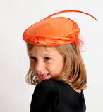 Dressup time. Young girl wearing fancy, orange women's hat Royalty Free Stock Photography