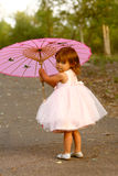 Dressy two-year-old girl carrying pink parasol. Cute multi-racial, 2 year old girl walks in a park and carries her blue stuffed bear.  Little girl is Asian/ Royalty Free Stock Images