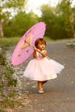 Dressy two-year-old girl carrying pink parasol. Cute, multi-racial, 2 year old girl walks in a park and carries a pink parasol.  Little girl is Asian/Caucasian Stock Photo