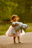 Dressy two-year-old girl carrying stuffed animal. Cute multi-racial, 2 year old girl walks in a park and carries her blue stuffed bear.  Little girl is Asian/ Stock Photo