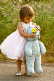 Dressy two-year-old girl in pink dress holding stuffed bear and flower. Cute, multi-racial, 2 year old girl wears a dressy, pale pink, full dress and holds a Royalty Free Stock Photos