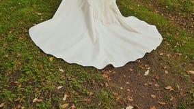 Drev av bröllopsklänningen av bruden på gräs Närbild bröllop för tappning för klädpardag lyckligt stock video