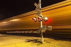 Drev som passerar en järnväg crossing vid natt Royaltyfria Bilder
