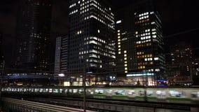 Drevet passerar över bron i centrala Tokyo Japan på natten lager videofilmer