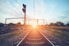 Drevplattform och trafikljus på solnedgången järnväg Järnvägst Royaltyfri Bild
