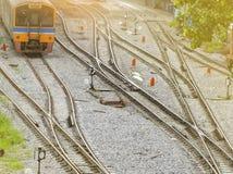 Drevspår och trafiktecken mellan järnvägen Resa med drevet i morgonen med varmt soluppgångljus lokalt trans royaltyfri bild