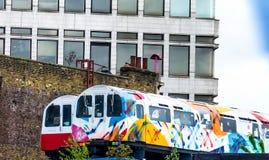 Drevstation Två bilar av ett passageraredrev målade med ljusa färger Vandalismteckningar på transport arkivbild