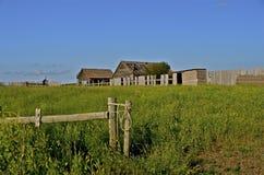 Drewna ogrodzenie otacza starych wietrzejących rolnych budynki Fotografia Stock