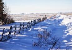 Drewna ogrodzenie wzdłuż śnieżnych dryfów Zdjęcia Royalty Free