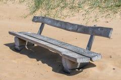 Drewniana ławka na piaskowatej plaży Szorstka drewniana ławka obrazy royalty free