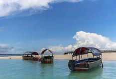 Drewniana łódź rybacka na piaskowatej plaży z błękitne wody tłem, Z obrazy royalty free
