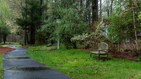 Drewniana ławka i birdhouse obok ścieżki obraz stock