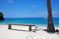 Drewniana ławka na białego piaska tropikalnej plaży na Malapascua wyspie, Filipiny zdjęcia stock