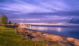 Drewniana ławka na jeziornym brzeg przy wschodem słońca Fotografia Royalty Free