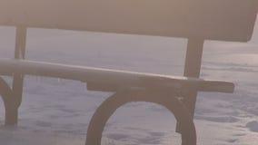 Drewniana ławka w parku na śniegu i ranek mgła z światłem słonecznym
