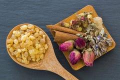 Drewniana łyżka aromatyczny żółty żywicy dziąsło obok wysuszonych kwiatów zdjęcia royalty free