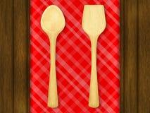 Drewniana łyżka i szpachelka na czerwonym w kratkę tablecloth tle ilustracja wektor