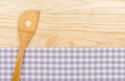 Drewniana łyżka na purpurowym w kratkę stołowym płótnie Zdjęcia Royalty Free