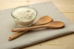 Drewniana łyżka, szpachelka i puchar z pszeniczną mąką na bieliźnianym napk Zdjęcia Stock