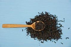 Drewniana łyżka z herbatą na błękita stole w rozsypisku Zdjęcia Royalty Free