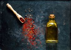 Drewniana łyżka z pikantność i oliwa z oliwek w szklanej butelce na tle starzy ośniedziali metale, żywności organicznej pojęcie, zdjęcia stock
