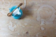 Drewniana łyżka z pojedynczym migdałem balansował przez wierzchołek błękitny ceramiczny miotacz migdału mleko obrazy stock