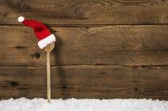 Drewniana łyżka z Santa kapeluszem: nieociosany bożego narodzenia tło Zdjęcie Royalty Free