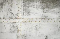 Drewniana ściana malował w bielu z żelaznymi talerzami na nim obrazy royalty free