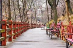 Drewniana ścieżka - zależący od most z mokrymi deskami, dokonanego żelaza ławkami i lampionami w parku na zboczu, przegapia białą zdjęcie stock