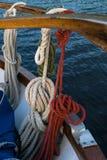 Drewniana żaglówka na błękitnym morzu śródziemnomorskim arkany, kępki i drewniana deska na pokładu tle, obraz stock