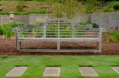 Drewniana ławka w irysa ogródzie Zdjęcia Royalty Free