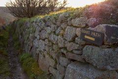 Drewniana brzegowa ścieżka podpisuje wewnątrz żółtego writing młotkującego kamienna ściana z widokiem brzegowa ścieżka w odległoś obraz stock