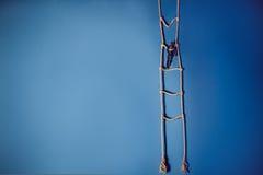 Drewniana ciemna mannequin pozycja na wiszącej linowej drabinie na jaskrawym błękitnym tle Życia pojęcie Selekcyjna ostrość Zdjęcie Stock