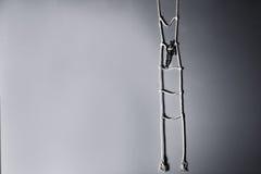 Drewniana ciemna mannequin pozycja na wiszącej linowej drabinie na szarym tle Życia pojęcie Monochrom, Selekcyjna ostrość Obrazy Stock