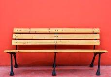 Drewniana długa ławka przeciw pustej czerwieni ścianie fotografia royalty free