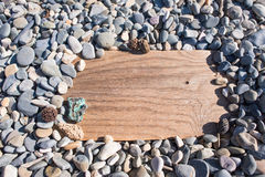 Drewniana deska w kamieniu na plaży Tło, billboard, piarg Obrazy Royalty Free