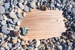 Drewniana deska w kamieniu na plażowym tle, billboard Fotografia Stock