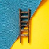 Drewniana drabina na żółtym i błękitnym tle Zdjęcie Stock