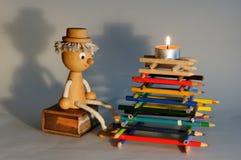 Drewniana figurka ogniskiem robić kolorów ołówki fotografia royalty free