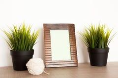 Drewniana fotografii rama obok dwa garnków trawa Obrazy Stock