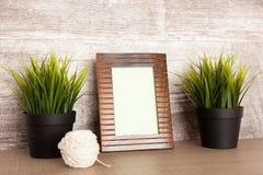 Drewniana fotografii rama obok dwa garnków trawa Zdjęcia Stock