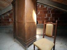 Drewniana garderoba i antykwarski krzesło w zakurzonym attyku Obrazy Royalty Free
