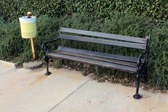 Drewniana jawna ławka z czarnymi żelazo stronami i żółtym kubeł na śmieci Zdjęcie Royalty Free